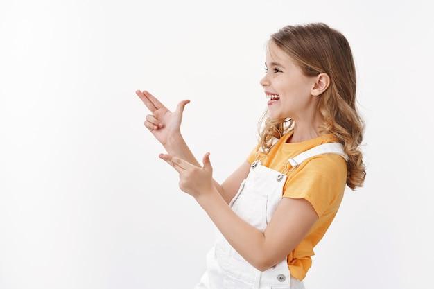 Gioiosa bambina carina che si diverte a giocare con gli amici, puntando le pistole con il dito, guardando fare il segno bang-bang lasciato sorridente e ridendo giocosamente, godersi le vacanze estive, in piedi muro bianco
