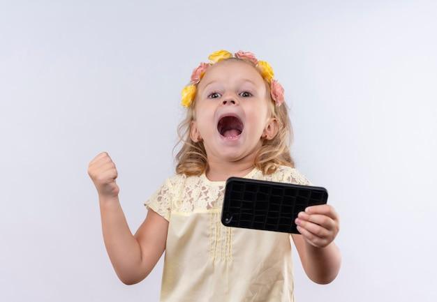 Una bambina sveglia allegra che indossa la camicia gialla in fascia floreale che solleva il pugno chiuso mentre tiene il telefono cellulare su una parete bianca