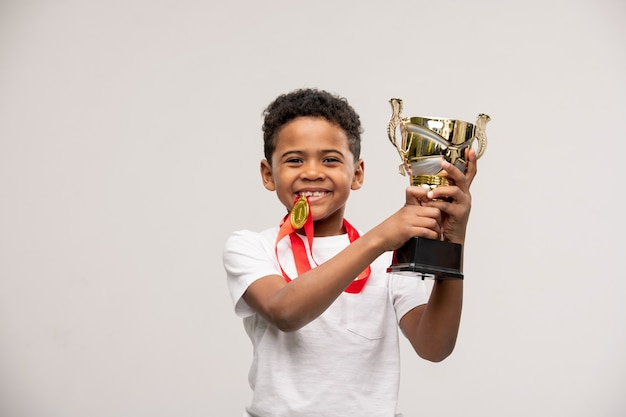 Joyful cute mixed-race little boy with medal and golden cup in hands standing with copyspace on his right and left
