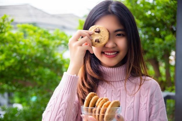 Joyful cute teenage holding cookie at home