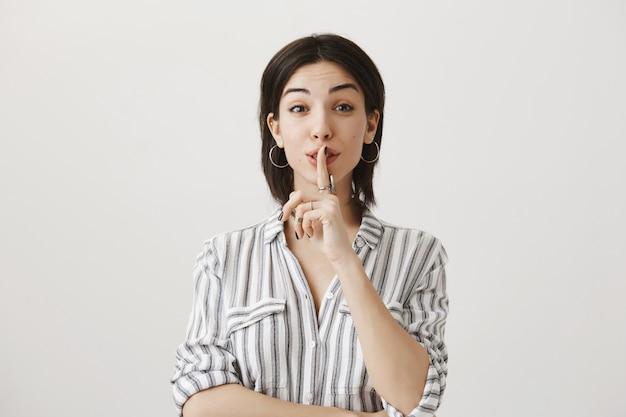 Gioiosa donna carina che zittisce, chiede di tacere o dice il segreto