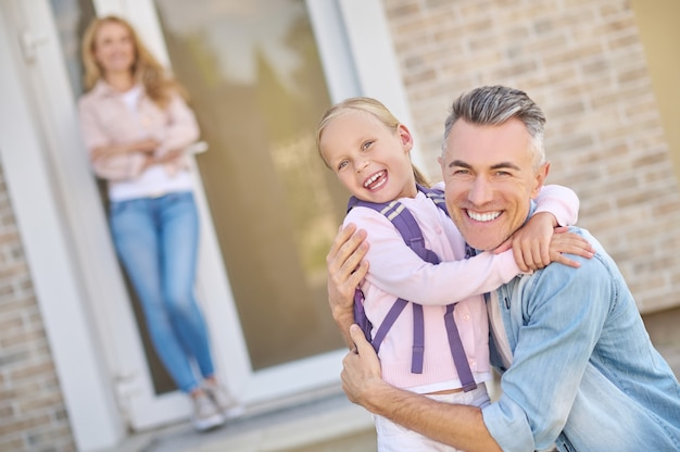 Joyful dad and daughter hugging near house