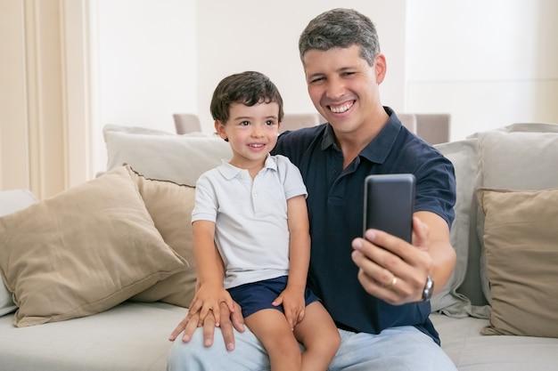 Papà gioioso e figlio piccolo che si godono il tempo libero insieme, seduti sul divano di casa, ridendo e prendendo selfie.
