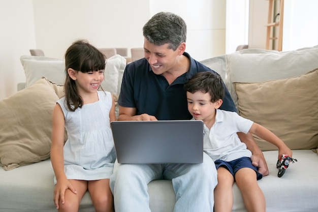 Joyful dad pointing at screen and showing content on laptop to happy kids.