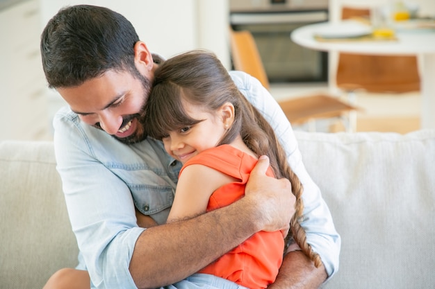Joyful dad sitting with his little girl on couch, hugging and cuddling her.
