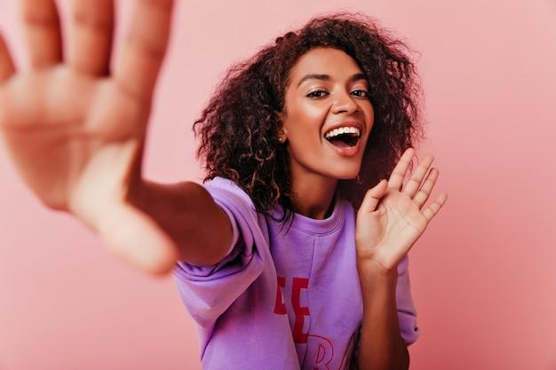 셀카를 만드는 동안 웃 고 즐거운 검은 눈 소녀. 놀라운 갈색 머리 아프리카 아가씨 스튜디오에서 장난.