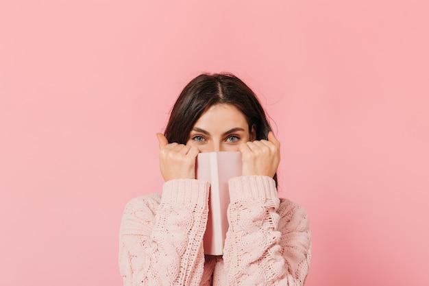 Радостная темноволосая девушка закрывает лицо розовой записной книжкой. женщина в вязаном свитере смотрит в камеру.
