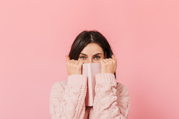 Joyful dark-haired girl covers her face with her pink notebook. woman in knitted sweater looks into camera.