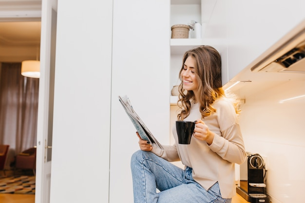 Joyful dark-haired lady spending morning at home, reading newspaper with smile