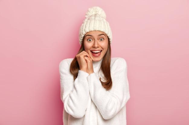 Радостная темноволосая миллениалка радостно реагирует на хорошие новости, широко улыбается, носит теплую зимнюю шапку и удобный белый свитер, с восторженным взглядом смотрит, изолирована на розовой стене