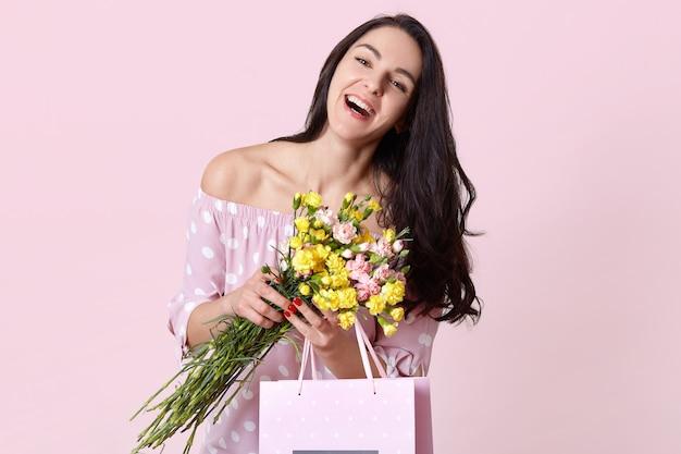 Радостная темноволосая барышня счастливо улыбается, одетая в стильную одежду, с удовольствием получает подарок на день рождения, держит букет цветов, модели на розовых тонах. концепция весеннего времени