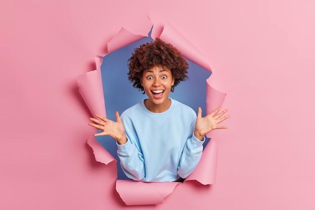 Радостная темнокожая афроамериканка в синем джемпере поднимает руки