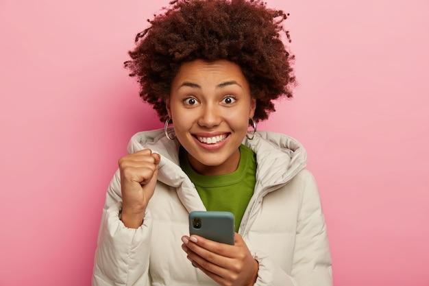 Gioiosa femmina dalla pelle scura celebra la buona notizia, vestita di capispalla, sorride felicemente posa sul muro rosa