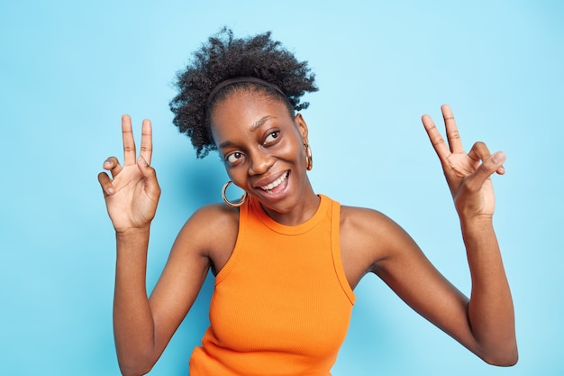 Joyful dark skinned female model dances with hands up partying with friends enjoys music on dance floor