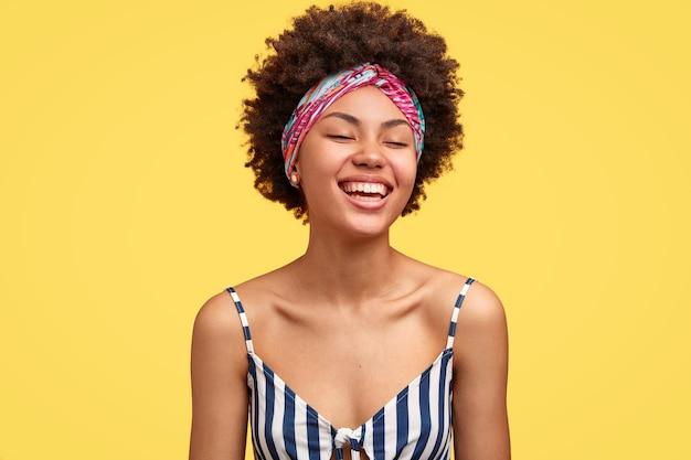 유쾌한 어두운 피부 모델은 유쾌하게 웃고, 행복에서 눈을 감고, 멋진 제안을 받고, 여름 여행 동안 기분이 좋아지고, 머리띠와 스트라이프 탑을 착용하고, 실내에서 포즈를 취합니다.