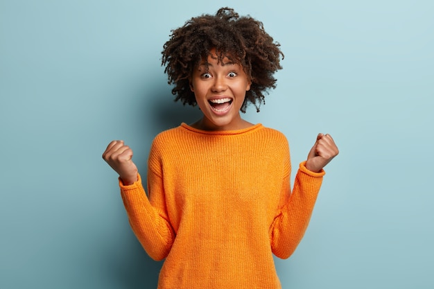 Joyful dark skinned model with crisp hair, clenches fists, feels overjoyed after winning game, wears orange jumper, poses over blue wall, expresses good emotions. people and success concept
