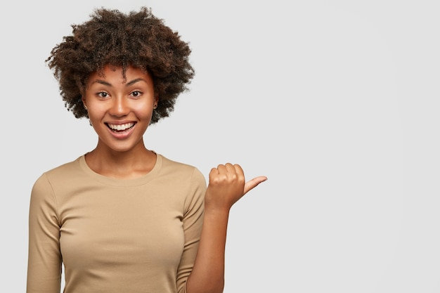 Joyful dark skinned smiling female has dark hair and curly hair, points aside with thumb