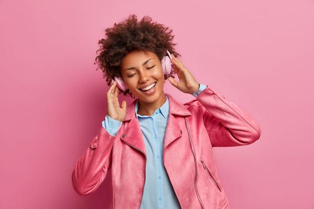 Joyful dark skinned woman has good mood listens music in stereo headphones closes eyes