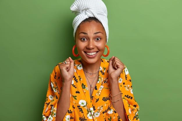 Радостная темнокожая женщина поднимает сжатые кулаки и радуется