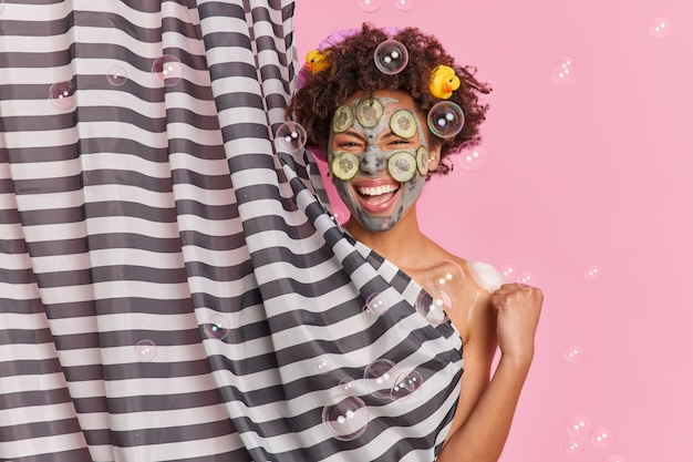 Joyful dark skinned woman with afro hair applies clay mask with cucumber slices clenches fist smiles broadly being in good mood while taking shower and undergoes facial treatments poses indoor