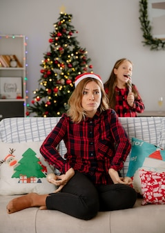 キャンディケインを食べるうれしそうな娘と怒っている母親はソファに座って、家でクリスマスの時間を楽しんでいるガラス玉の飾りを持っています