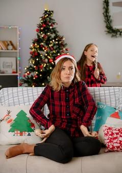 La figlia allegra che mangia il bastoncino di zucchero e la madre arrabbiata tiene gli ornamenti della sfera di vetro che si siedono sul divano e si godono il periodo natalizio a casa