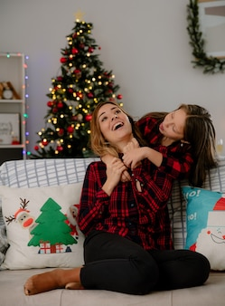 うれしそうな娘が舌を突き出し、自宅でクリスマスの時間を楽しんでいる後ろからソファに座っている母親を抱きしめます