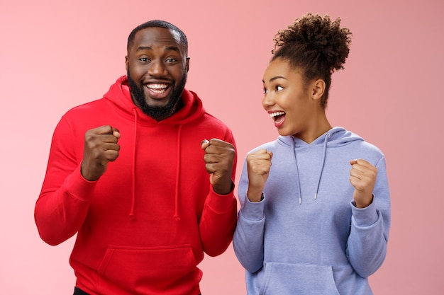 Joyful delighted celebrating african-american woman man standing together happy triumphing clenching fists cheering for favorite team watching match supporting fans celebrating goal win bet