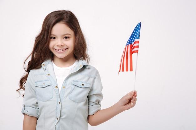 Радостная, довольная жизнерадостная девушка держит американский флаг, выражая позитив и стоя изолированной в белой стене