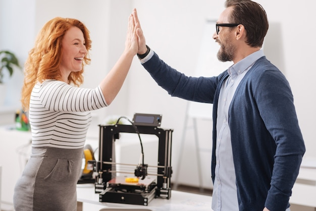 Радостные довольные счастливые коллеги смотрят друг на друга и дают пять при завершении своего проекта