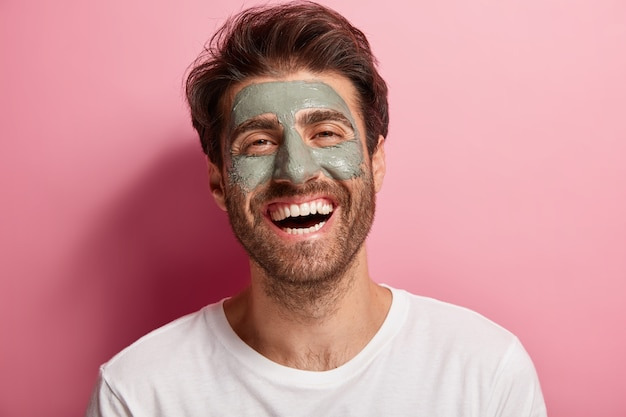 Joyful delighted man has clay mask on face, enjoys spa treatments, has broad smile, being in high spirit, cares about beauty