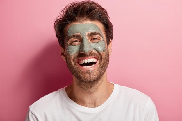 うれしそうな喜びの男は、顔にクレイマスクを持っていて、スパトリートメントを楽しんで、広い笑顔を持って、元気で、美しさを気にしています