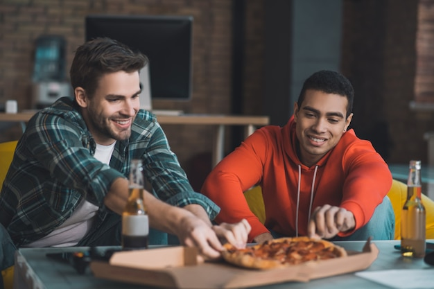 Радостные довольные мужчины развлекаются за пиццей дома