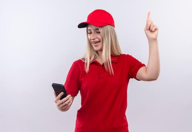彼女の手で電話を見ている赤いtシャツとキャップを身に着けているうれしそうな配達の若い女性は、孤立した白い壁の上を指しています