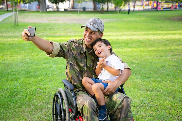 Joyful disabled military dad and his little son taking selfie together in park. boy sitting on dads lap. veteran of war or disability concept
