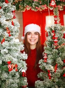Joyful dreamy santa woman on scene christmas tree with decor