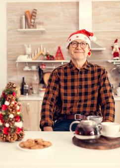 Радостный пожилой пожилой мужчина улыбается празднует рождество