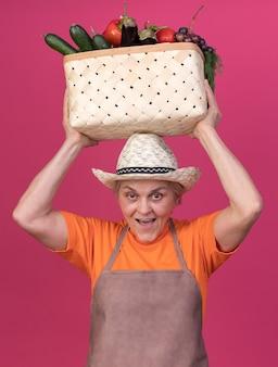 머리 위에 야채 바구니를 들고 원예 모자를 쓰고 즐거운 노인 여성 정원사