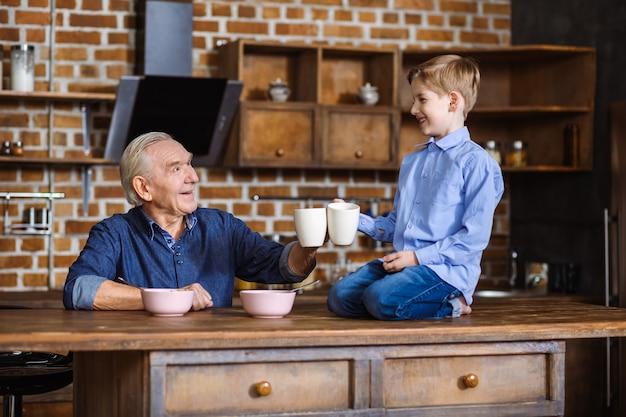 Радостный пожилой мужчина пьет чай во время завтрака с внуком