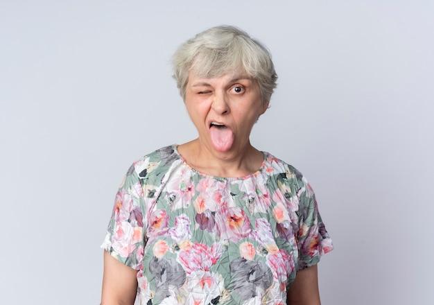 즐거운 노인 여성이 눈을 깜박이고 흰 벽에 고립 된 혀를 튀어 나와
