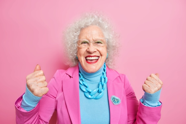 Joyful elderly woman clenches fists does winner gesture feels triumph smiles broadly wears bright makeup fashionable clothes