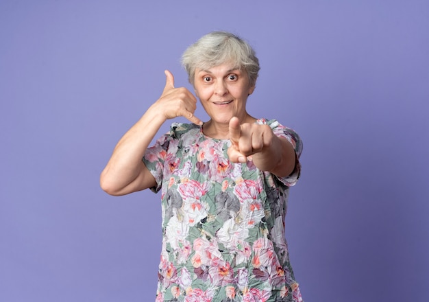 Joyful elderly woman gestures call me sign and points isolated on purple wall