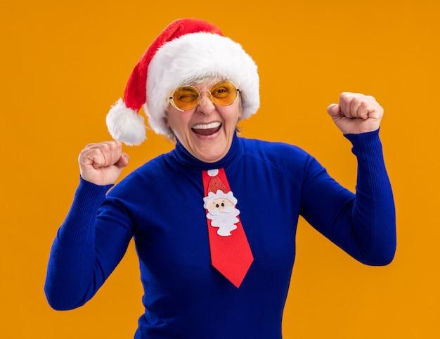 산타 모자와 산타 넥타이와 태양 안경에 즐거운 노인 여성 복사 공간 오렌지 배경에 고립 주먹을 유지