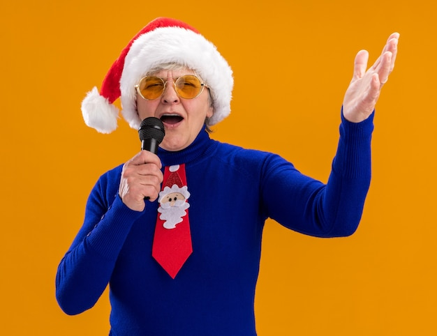 Joyful elderly woman in sun glasses with santa hat and santa tie holds mic pretending to sing isolated on orange background with copy space