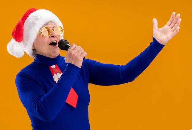 La donna anziana allegra in occhiali da sole con cappello da babbo natale e cravatta da babbo natale tiene il microfono fingendo di cantare guardando il lato isolato sulla parete arancione con spazio di copia