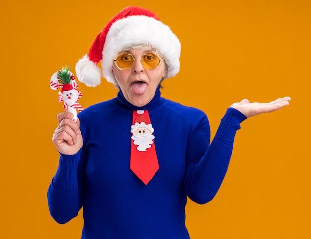 La donna anziana allegra in occhiali da sole con cappello da babbo natale e cravatta da babbo natale sporge la lingua e tiene un bastoncino di zucchero isolato sulla parete arancione con spazio di copia
