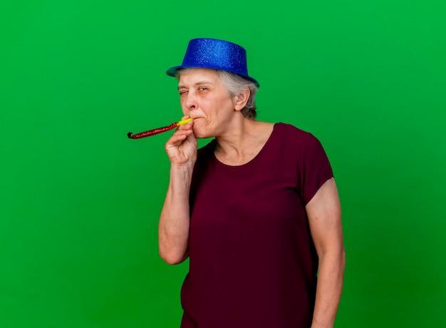 Joyful elderly woman wearing party hat blinks eye blowing whistle on green
