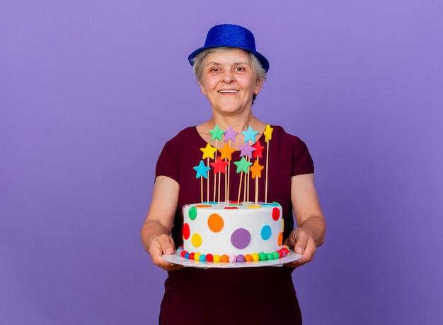 파티 모자를 쓰고 즐거운 노인 여성이 보라색 벽에 고립 된 생일 케이크를 보유하고 있습니다.