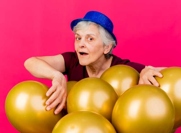 ピンクのヘリウム気球の後ろにパーティーハットをかぶってうれしそうな年配の女性が立っています