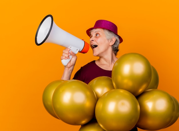 Joyful elderly woman wearing party hat stands with helium balloons speaking into loud speaker looking at side isolated on orange wall